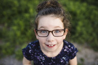 Portrait of cute girl wearing eye glasses looking up at camera - ISF04473