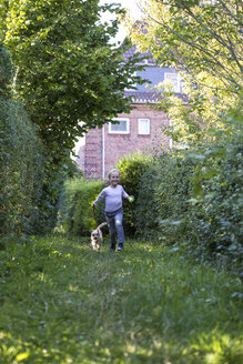 Little girl running on a meadow with her mongrel - JFEF00867