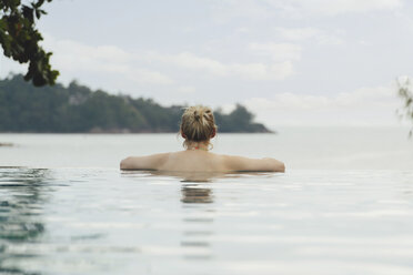 Thailand, Phuket, back view of woman relaxing in infinity pool - CHPF00466