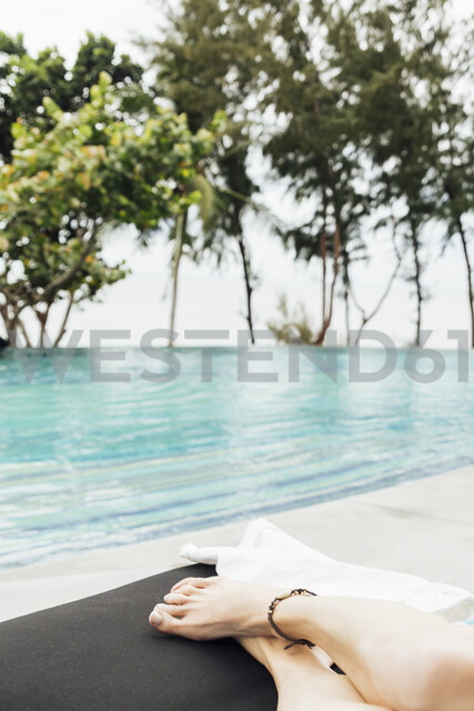 Thailand, legs of woman relaxing at pool - CHPF00469