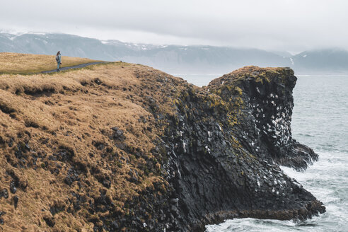 Iceland, young hiker looking at coast - KKAF01013