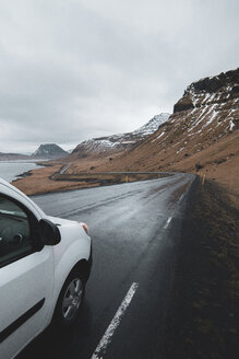 Iceland, white car on wet coastal road - KKAF01016