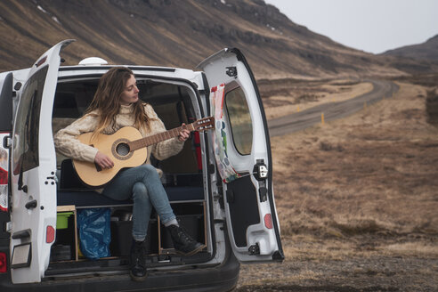 Iceland, woman in front of van playing guitar - KKAF01025