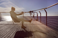Man practicing suspension training on a promenade around the sea - SKCF00454