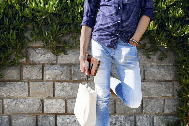 Man holding shopping bags by brick wall - ISF04570