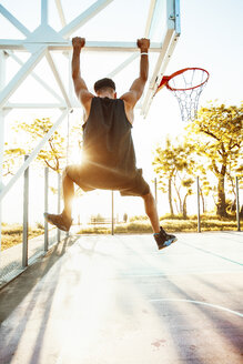 Young man on basketball court, swinging on basketball net frame, rear view - ISF04576