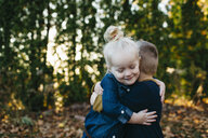 Cute female toddler hugging twin brother in autumn garden - ISF04588