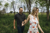 Romantic couple holding hands in field - ISF04594