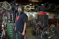 Portrait of mature man holding wrench in bicycle workshop - ISF04603