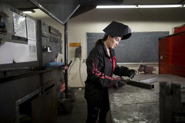 Female metalsmith examining metal rod at workshop bench - ISF04609