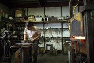 Male metalsmith hammering metal on workshop anvil - ISF04615