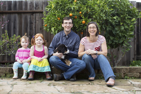 Portrait of young family with dog, sitting in garden - ISF04642