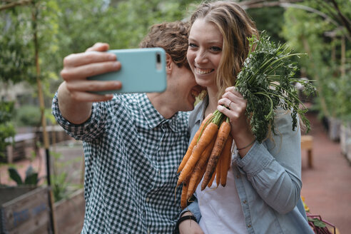 Couple in garden with carrots, taking selfie - ISF04678