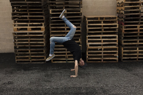 Young male street dancer doing handstand in front of stacked pallets - ISF04723