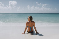Rear view of woman in bikini sitting on beach looking out at blue sea, Anguilla, Saint Martin, Caribbean - ISF04726