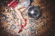 Woman lying on floor at party, surrounded by glitter, champagne bottle and disco ball, overhead view - ISF04772