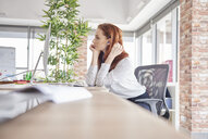 Woman sitting at desk looking away - ISF04787