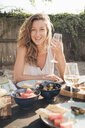 Portrait of young woman, outdoors, sitting at table, holding wine glass - ISF04832