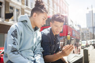Two young men outdoors, looking at smartphone - ISF04865