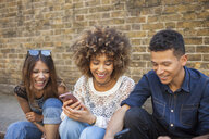 Three friends sitting in street, looking at smartphone - ISF04877