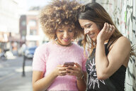Two young women in street, looking at smartphone - ISF04904