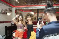 Three friends in diner, young man taking photograph of female friends, using smartphone - ISF04937