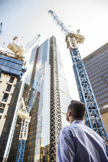 Businessman looking up at building under construction, London, UK - ISF05015