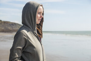 Young woman on beach in hooded top, Folkestone, UK - ISF05066