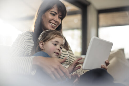 Woman with daughter on sofa looking at digital tablet - ISF05078