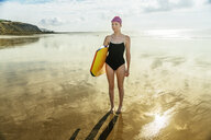 Young woman carrying surfboard on beach, Folkestone, UK - ISF05114