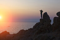 Silhouette of man on rocks looking away at sunset over sea, Olbia, Sardinia, Italy - ISF05201