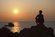 Silhouette of man on rocks looking away at sunset over sea, Olbia, Sardinia, Italy - ISF05225