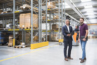 Warehouse worker and manager looking from aisle in distribution warehouse - ISF05363