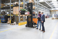 Warehouse worker talking by forklift truck in distribution warehouse - ISF05369