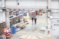 High angle view of supervisor and manager walking through distribution warehouse - ISF05444