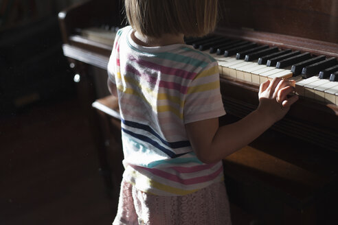 Rear mid section view of girl standing playing old piano at home - ISF05459