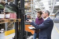 Manager pointing at forklift truck pallet in distribution warehouse - ISF05507