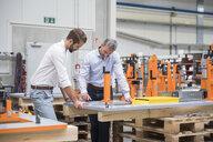 Two engineers looking at digital tablet in engineering factory - ISF05510