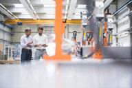 Two engineers looking at digital tablet in engineering factory - ISF05513