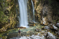 Hiker looking at waterfall, Accursed mountains, Theth, Shkoder, Albania, Europe - ISF05522