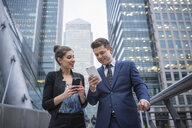 Businessman and businesswoman using mobile phone, Canary Wharf, London, UK - ISF05606
