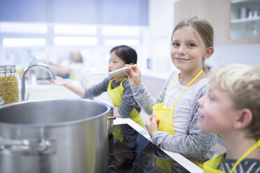 Portrait of smiling schoolgirl with classmtes in cooking class - WESTF24082