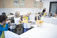 Pupils cooking together in cooking class - WESTF24088