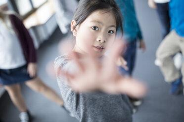 Portrait of schoolgirl raising her hand - WESTF24097