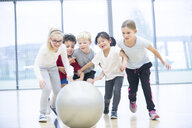 Happy pupils playing with gym ball in gym class - WESTF24100