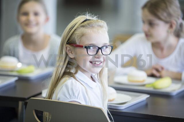 Portrait of smiling schoolgirl with classmates in school canteen - WESTF24106