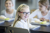 Portrait of smiling schoolgirl with classmates in school canteen - WESTF24106