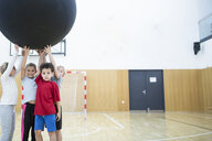 Pupils holding big ball in gym class - WESTF24112