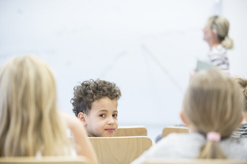 Portrait of schoolboy with classmates and teacher in class - WESTF24115