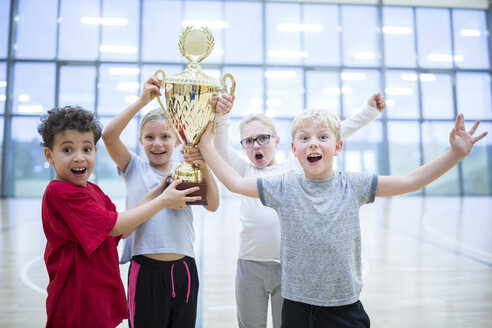 Happy pupils holding trophy in gym - WESTF24118